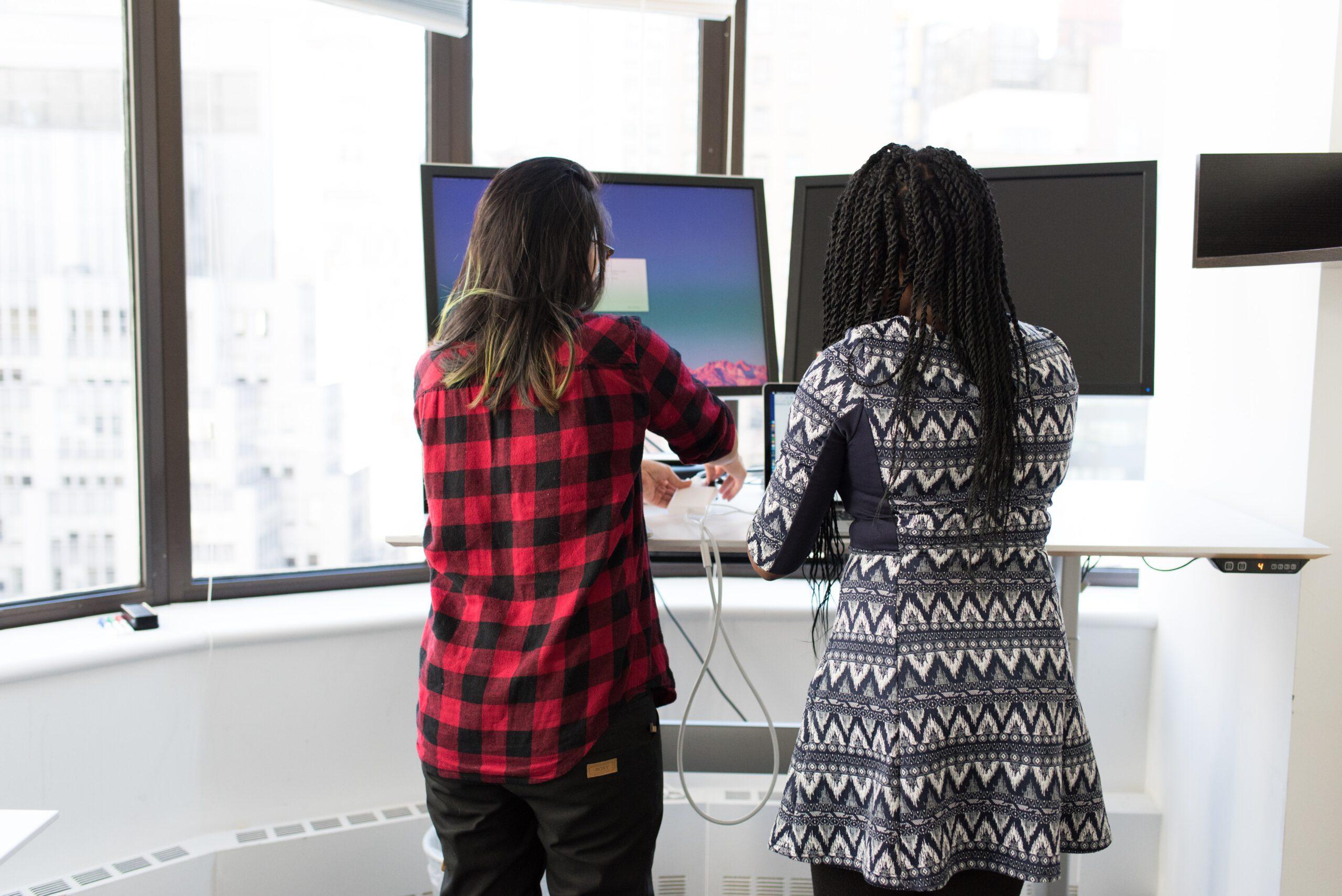 Deux personnes debout devant des ordinateurs.